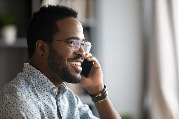 Smiling young adult african american hipster business man professional making business call talking on the phone in office enjoying corporate mobile conversation indoors, closeup side profile view